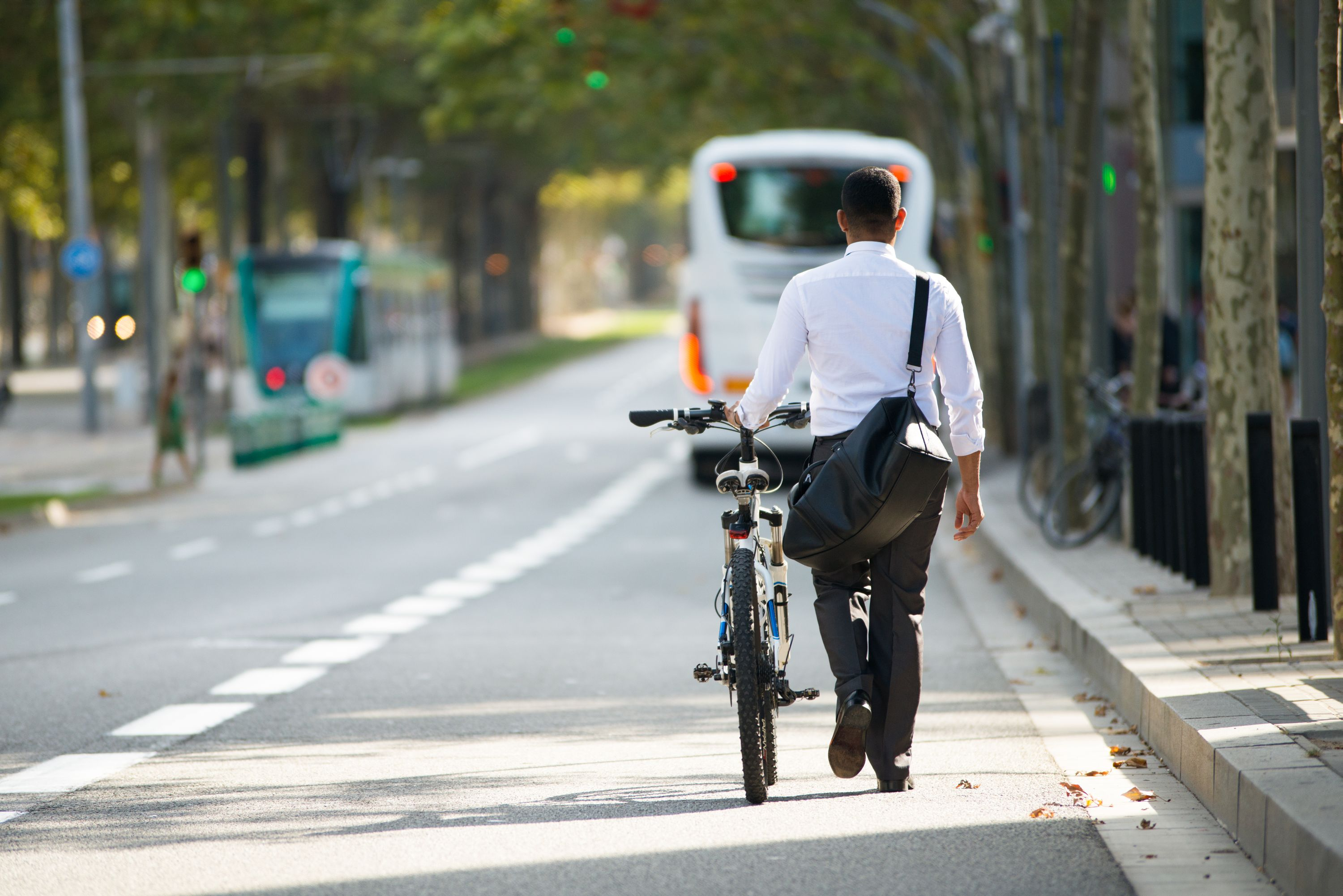 Back view of businessman walking with shoulder bag and bike in street. Young male office employee going after work. Lifestyle concept